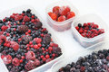 Plastic containers of frozen mixed berries in snow Stock Photos