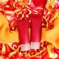 Plastic cream tubes over motley cloth Royalty Free Stock Photo
