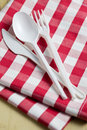 Plastic cutlery on checkered tablecloth Royalty Free Stock Photos