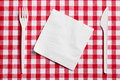 Plastic cutlery on checkered tablecloth Royalty Free Stock Photo
