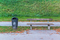 Plastic dust bin in the park and wooden chair Royalty Free Stock Image