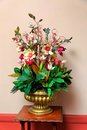 Plastic flower arrangement in golden vase Royalty Free Stock Photo