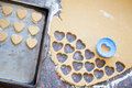 Plastic heart shaped cookie cutter and raw dough cookies on meta blue metal baking tray Royalty Free Stock Image