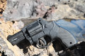 Plastic revolver gun toy on the volcanic rocks Royalty Free Stock Images