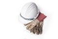 Plastic safety helmet and dirty old leather gloves on white background Royalty Free Stock Image