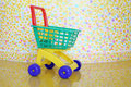 Plastic shopping trolley and stylish wall with varicoloured brush strokes in kids room Royalty Free Stock Image