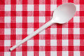 Plastic spoon on checkered tablecloth Stock Image