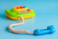 Plastic toy mobile phone on a blue background for children. Royalty Free Stock Photo