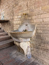 Plastic water bottle discarded by ancient drinking fountain thrown away next to an and ornate in assisi showing how wasteful man Royalty Free Stock Photos
