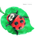 Plasticine cartoon ladybug seeting on a green leaf on a white background Royalty Free Stock Images