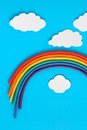 Plasticine rainbow near white paper clouds blue background Royalty Free Stock Image