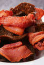 Plasticity black bread and meat slices the fried thin of bacon heap macro Stock Photography