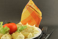 Plate with baby potatoes and tomato white roasted lettuce mayonnaise dressing close up orange napkin fork knife steel Stock Images