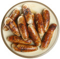 Plate of bbq cooked sausages chargrilled pork piled on a Royalty Free Stock Photos