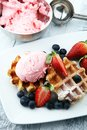 Plate of belgian waffles with strawberry ice cream, and fresh st Royalty Free Stock Photo