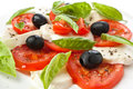 Plate of classic caprese salad with black olives Stock Images