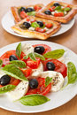 Plate of classic caprese salad with black olives and puff pastry pies in the back Royalty Free Stock Photography