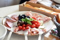Plate of cold cuts goat cheese tomatoes black olives cherry ham and salami Royalty Free Stock Photo
