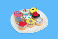 A plate with colorful cup cakes isolated on blue background Royalty Free Stock Photo