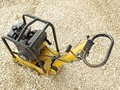 Plate compactor old yellow on aggregate bed Stock Photo