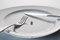 Plate with cutlery and a pea Royalty Free Stock Photo