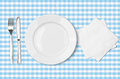 Plate fork knife and napkin over blue tableclot checked fabric tablecloth top view Stock Images