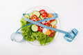 Plate with fresh vegetables salad and measured tape isolated on Royalty Free Stock Photo