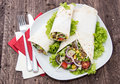 Plate with fresh wraps on wooden background Stock Photo