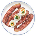 Plate of Fried Bacon Rashers with hard boiled Egg slices Isolated Royalty Free Stock Photo