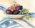 Plate with fruit grapes and plums on a cloth a blue pattern Royalty Free Stock Photo