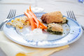 Plate full of delicious food and two forks on a table Royalty Free Stock Photo