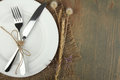 Plate, knife and fork tied with twine and dried flowers and bur Royalty Free Stock Photo