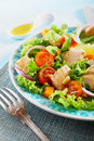 Plate with a mediterranean chicken salad healthy pine seeds lettuce cherry tomatoes onions basil and lemon on blue fork in Stock Images