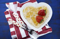 Plate of nutritious and healthy cooked breakfast oats with strawberries honey in heart shaped bowl on dark blue rustic wood Royalty Free Stock Photography