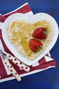 Plate of nutritious and healthy cooked breakfast oats with strawberries honey in heart shaped bowl on dark blue rustic wood Stock Image
