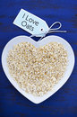 Plate of nutritious and healthy oat flakes in heart shaped bowl on dark blue rustic wood table with i love oats message tag Royalty Free Stock Photo