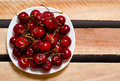 Plate with red cherries on wooden plates, top view, space for text Royalty Free Stock Photo