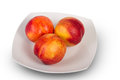 Plate of ripe nectarines delicious juicy on white Stock Photography