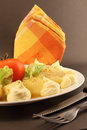 Plate with roasted baby potatoes white lettuce and tomato mayonnaise dressing close up orange napkin fork and knife steel Royalty Free Stock Photo