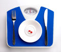 Plate on scale for dieting concept white with supplement spoon and knife blue top view Royalty Free Stock Photo