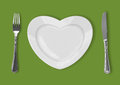 Plate in shape of heart, table knife and fork on green backgroun Stock Image
