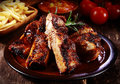 Plate of spicy marinated grilled spare ribs delicious or barbecued served with french fries and tomato at a steakhouse or Royalty Free Stock Image
