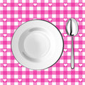 Plate with a spoon on a pink tablecloth Royalty Free Stock Image