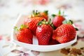 Plate of strawberries on a table cloth Stock Image