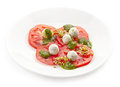 Plate of tomato and goat cheese balls salad on a white background Royalty Free Stock Photo