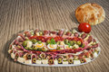 Plateful of serbian appetizer meze with pita bread and tomato on domestic loaf placed wooden table Stock Image