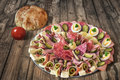 Plateful of serbian appetizer meze with pita bread and tomato on plate domestic loaf placed very old weathered cracked scratched Royalty Free Stock Photo