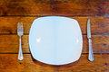Plates and cutlery on wooden table top view Royalty Free Stock Photos