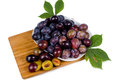 Platter of fresh ripe plums high angle view a with green leaves on a wooden board displaying halved isolated on Royalty Free Stock Photo