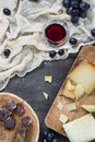 Platter with hard cheeses and homemade dried meat, glass of red wine with grapes